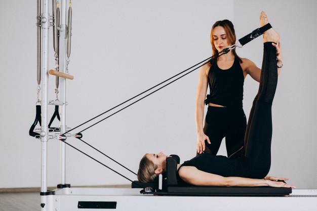 profesora de pilates realizando clase particular de reformer a su cliente