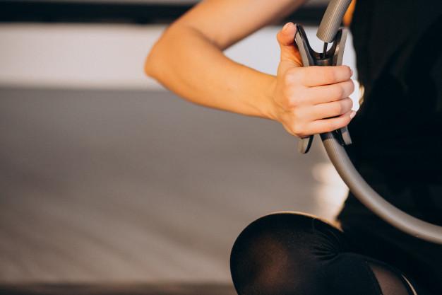 mujer sujetando un aro de pilates