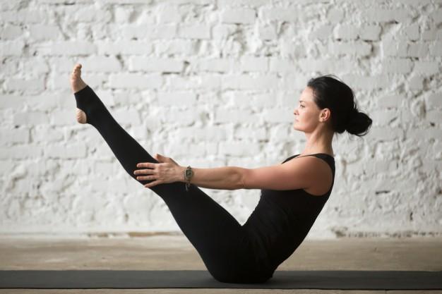 mujer realizando ejercicio teaser de pilates